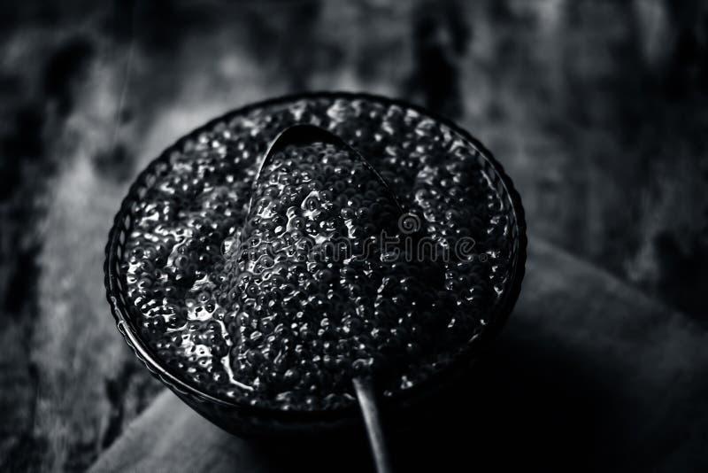 Semillas empapadas de la albahaca dulce o semillas del sabja en un bol de vidrio en superficie de madera imagen de archivo libre de regalías