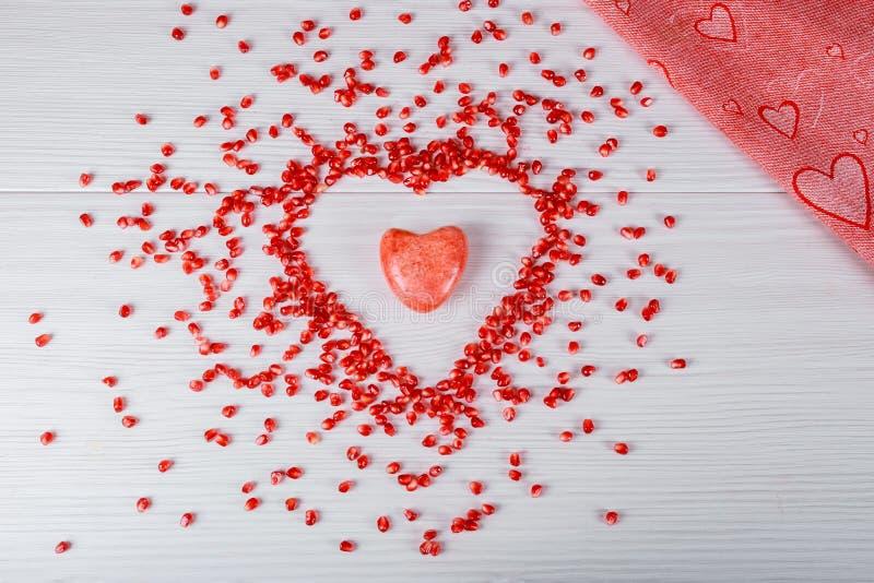 Semillas en forma de corazón de la granada del amor imagenes de archivo