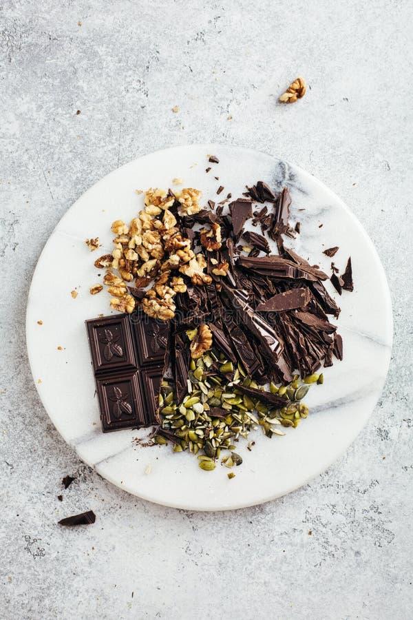 Semillas oscuras del chocolate, de la nuez y de calabaza en un tablero de mármol fotos de archivo libres de regalías
