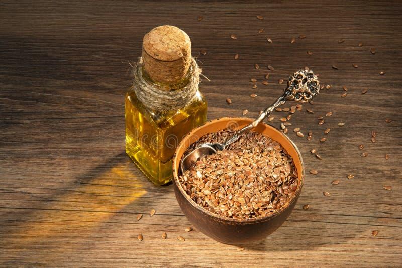 Semillas y aceite de lino en una tabla imagenes de archivo