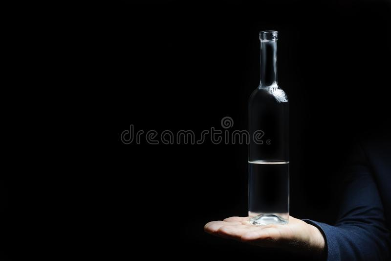 Semillena es una botella vacía de vodka en un fondo negro foto de archivo