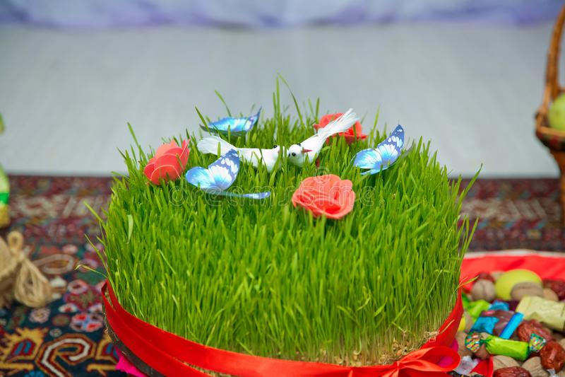 A seminal floor on a red ribbon on a dry grass . Novruz national Azerbaijan holiday spring new year celebration concept, wheat gra. Novruz national Azerbaijan royalty free stock photo