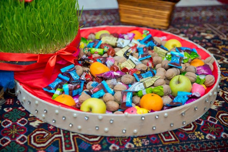 A seminal floor on a red ribbon on a dry grass . Novruz national Azerbaijan holiday spring new year celebration concept, wheat gra. Novruz national Azerbaijan stock image