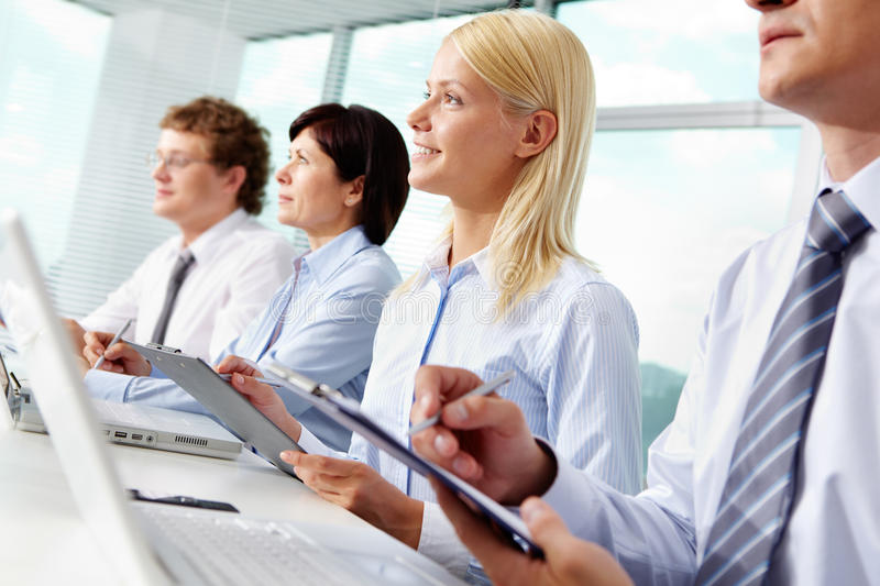 At seminar. Young female making notes at seminar with business partners near by royalty free stock images