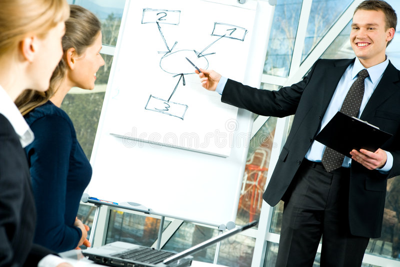 At seminar. Two business women looking at whiteboard while the man showing his project stock photography