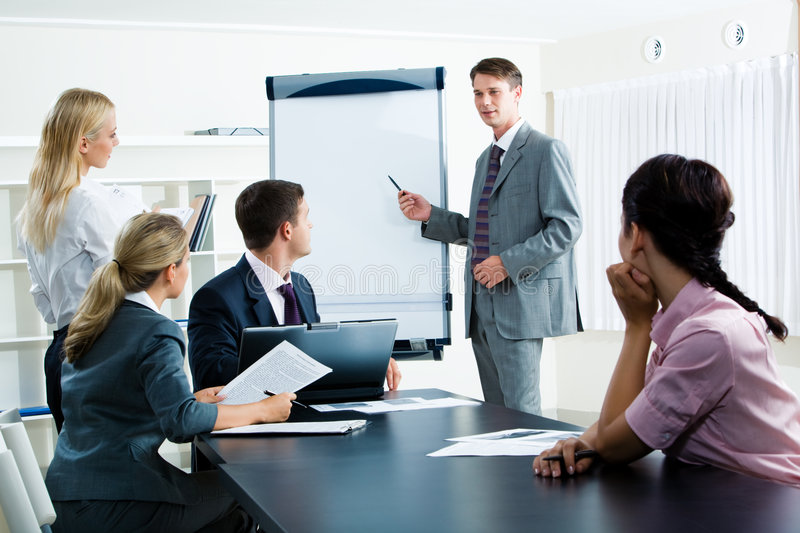 Seminar. Image of smart business people looking at their leader while he explaining something on whiteboard during seminar
