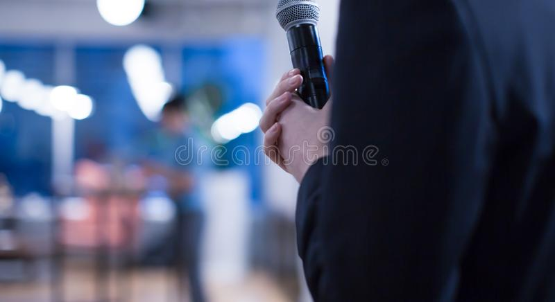 Seminar presenter`s hand holding microphone at conference giving speech. Speaker giving lecture to business audience. stock photography