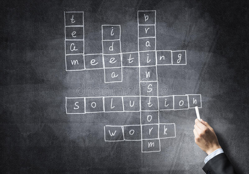 Seminar trainer draw on chalkboard. Business concept with crossword drawn with chalk on blackboard stock image