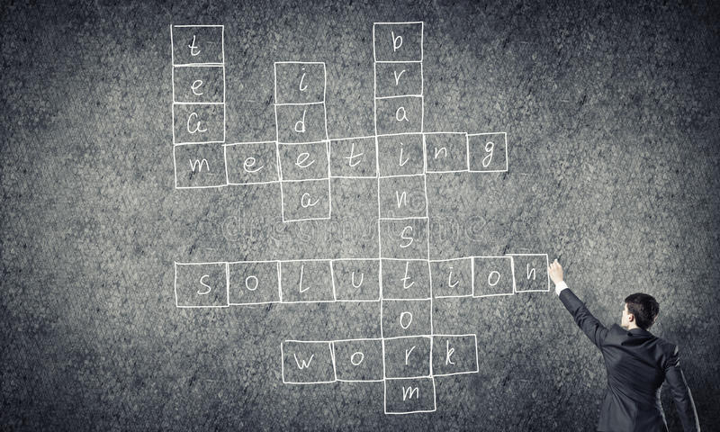Seminar trainer draw on chalkboard. Businessman standing with back and drawing crossword on blackboard royalty free stock image