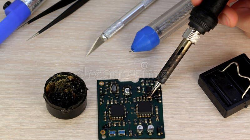 Seminarium på reparation av hushållanordningar, elektronik och processorer löda brädelödkolv som beträffande-löder chiper, royaltyfri foto