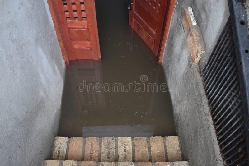 Seminterrato sommerso dopo la pioggia massiccia Cantina sommersa con la porta di legno in pieno di acqua sporca immagine stock libera da diritti