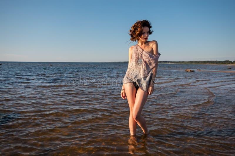 Seminude женщина против предпосылки моря стоковые изображения
