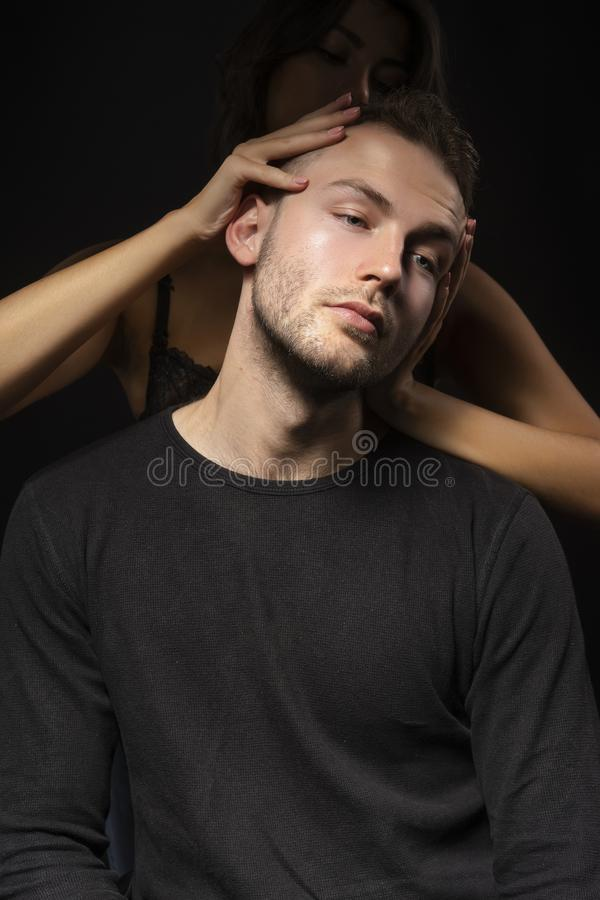 Seminude girl hidden in the dark, wearing only a bra does a head. Massage to a young stylish men with stubble on his face. Fashion, advertising and commercial stock photos