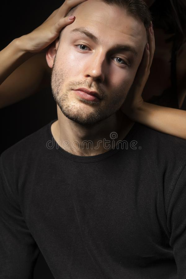 Seminude girl hidden in the dark, wearing only a bra does a head. Massage to a young stylish men with stubble on his face. Fashion, advertising and commercial royalty free stock photos
