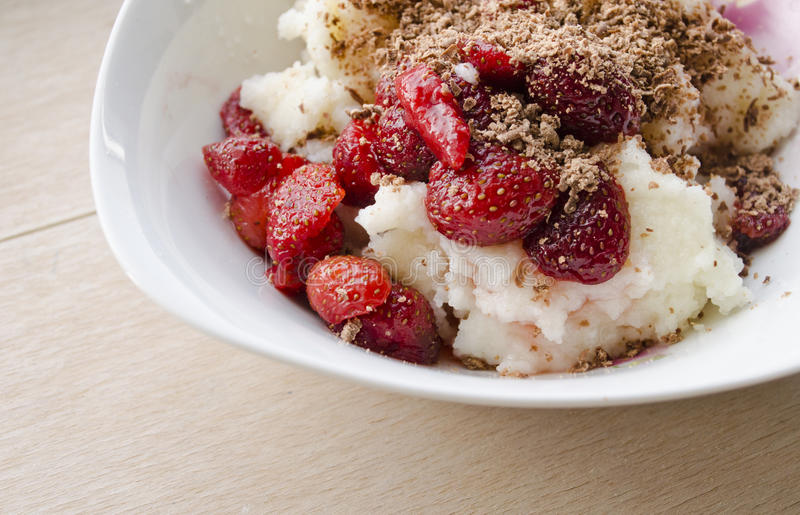 Semolina pudding served with fresh fruit strawberries and sprinkled with grated chocolate royalty free stock photography