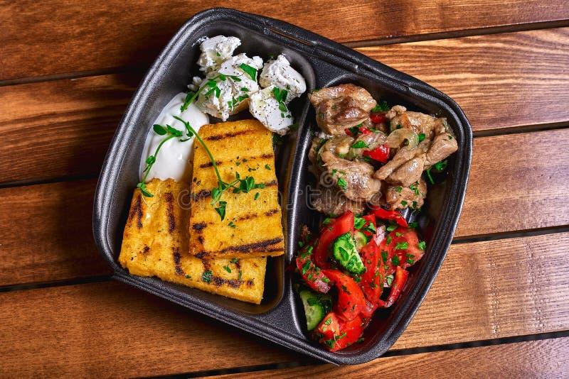Semoule de maïs avec du porc, le boeuf et la salade de ragoût de viande dans les plats en plastique Nourriture de rue L'espace li photo stock