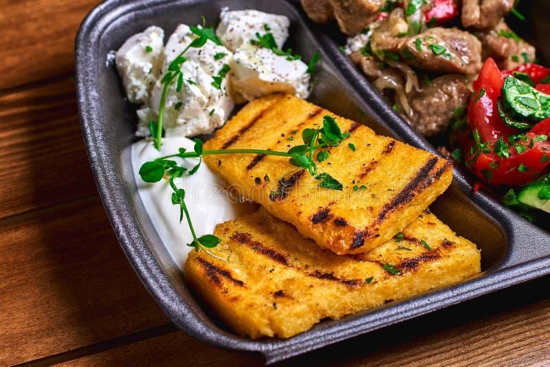 Semoule de maïs avec du porc, le boeuf et la salade de ragoût de viande dans les plats en plastique Nourriture de rue L'espace li photos libres de droits