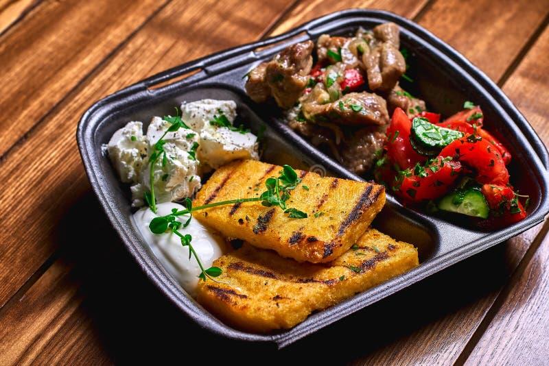 Semoule de maïs avec du porc, le boeuf et la salade de ragoût de viande dans les plats en plastique Nourriture de rue L'espace li photo libre de droits