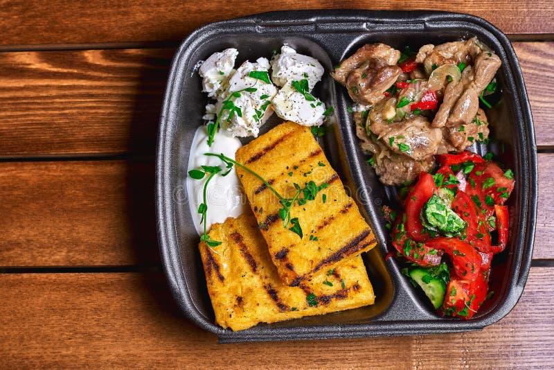 Semoule de maïs avec du porc, le boeuf et la salade de ragoût de viande dans les plats en plastique Nourriture de rue L'espace li image stock