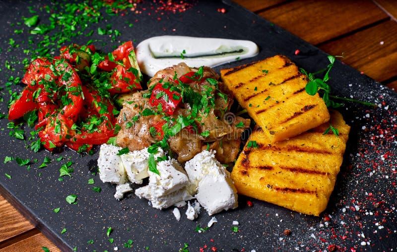 Semoule de maïs avec du porc, le boeuf et la salade de ragoût de viande sur un conseil noir Le dîner de mariage avec de la viande photo stock