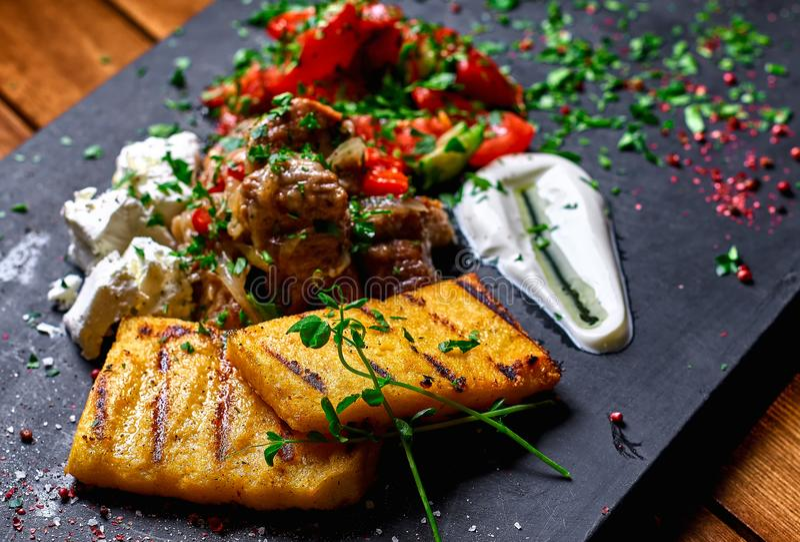 Semoule de maïs avec du porc, le boeuf et la salade de ragoût de viande sur un conseil noir Le dîner de mariage avec de la viande photos libres de droits