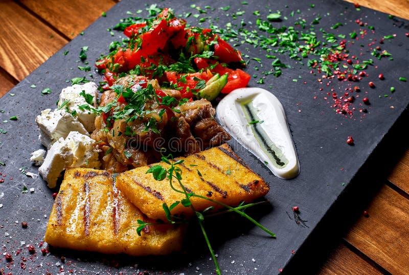 Semoule de maïs avec du porc, le boeuf et la salade de ragoût de viande sur un conseil noir Le dîner de mariage avec de la viande image libre de droits