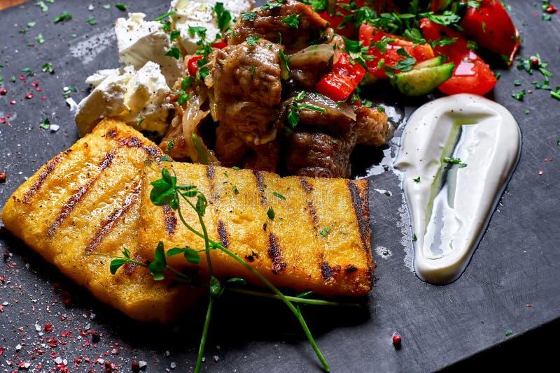 Semoule de maïs avec du porc, le boeuf et la salade de ragoût de viande sur un conseil noir Le dîner de mariage avec de la viande photos stock