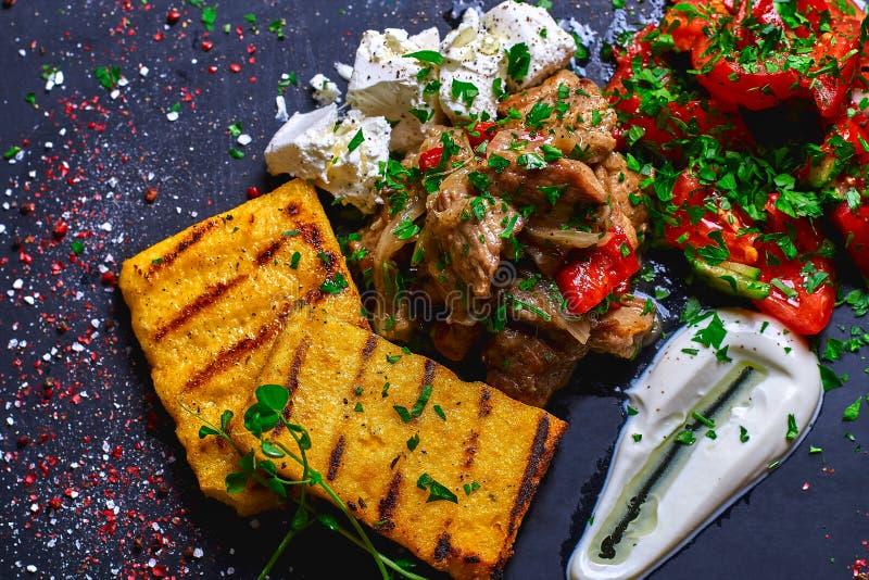 Semoule de maïs avec du porc, le boeuf et la salade de ragoût de viande sur un conseil noir Le dîner de mariage avec de la viande images stock