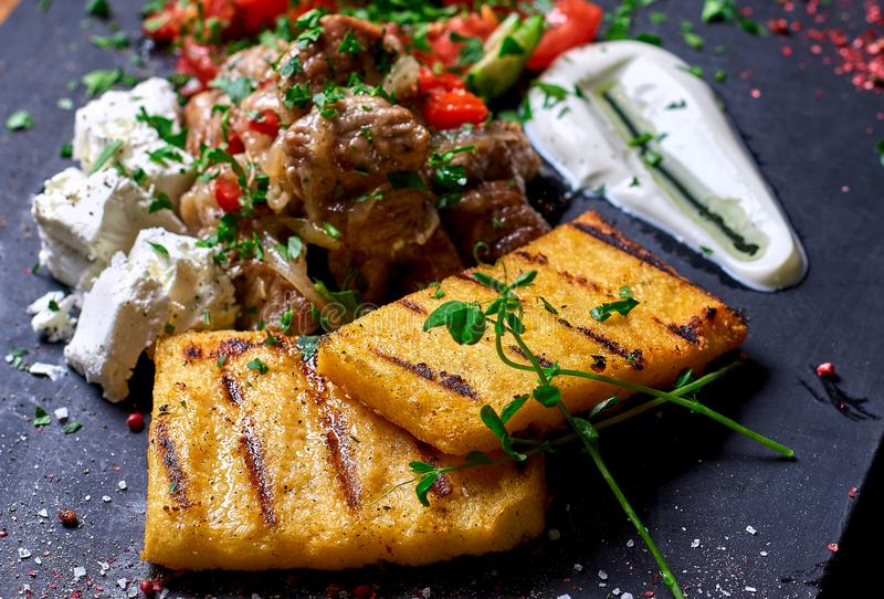 Semoule de maïs avec du porc, le boeuf et la salade de ragoût de viande sur un conseil noir Le dîner de mariage avec de la viande photo libre de droits