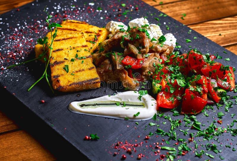Semoule de maïs avec du porc, le boeuf et la salade de ragoût de viande sur un conseil noir Le dîner de mariage avec de la viande photographie stock libre de droits