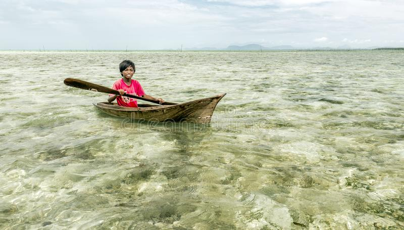 Bajau tribe kids having fun by rowing small boat near their village houses in Sea, Sabah Semporna, Malaysia stock image