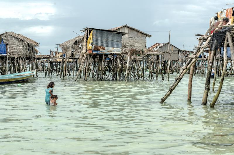 Bajau tribal girl carrying her brother to her home before he gets sunk in the sea, Sabah Semporna, Malaysia stock images