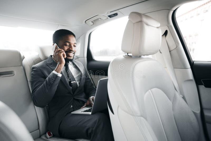 Sempre disponível Jovem empresário trabalhando em laptop no carro imagens de stock royalty free