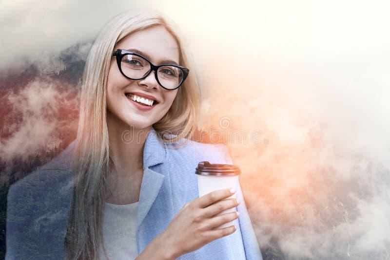 Sempre nell'umore positivo! Ritratto alto vicino di signora allegra di affari nella tazza di caffè della tenuta del vestito e nel fotografia stock libera da diritti