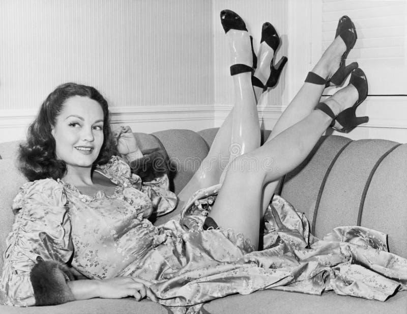 Sempre piacevole per avere un pezzo di ricambio, una giovane donna si siede sul suo sofà con quattro gambe (tutte le persone rapp fotografie stock