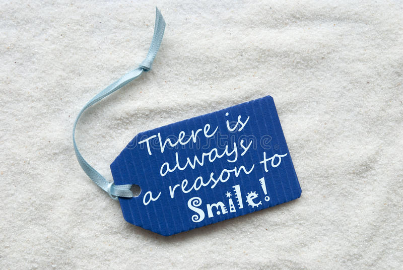 Sempre razão sorrir no fundo azul da areia da etiqueta imagens de stock royalty free