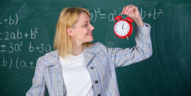 Sempre in tempo Sveglia della tenuta dell'insegnante della donna Si preoccupa per disciplina Tempo di studiare Anno scolastico be fotografia stock libera da diritti