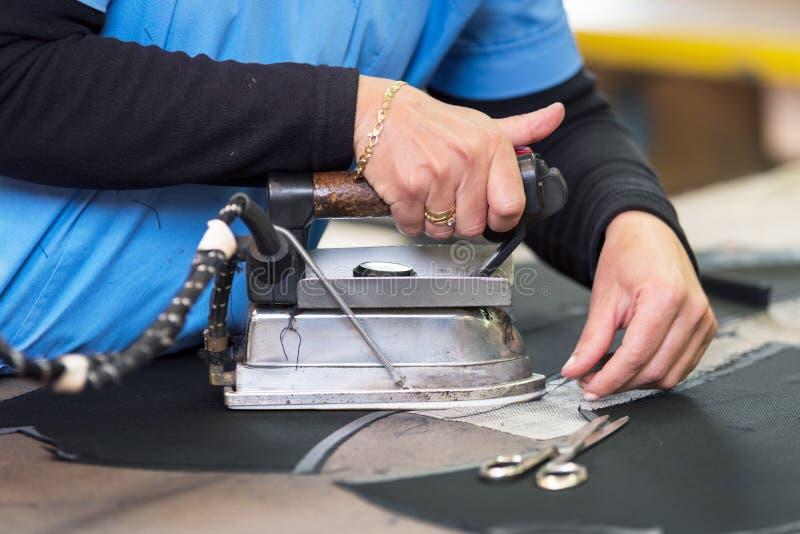 Semstress ironing the fabric. seamstress irons fabirc in a sewing workshop. Semstress ironing the fabric. seamstress irons fabirc in a sewing workshop royalty free stock photo