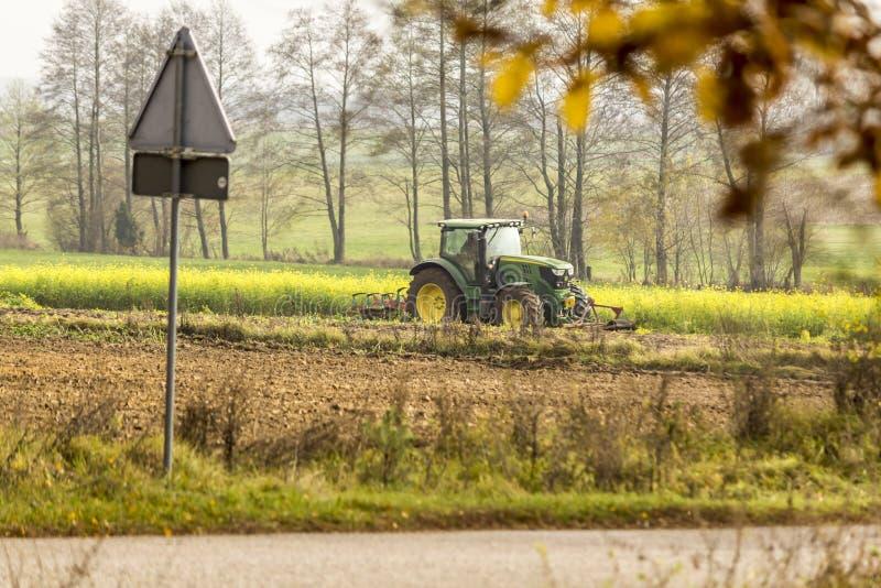 Sen höst Jaga Traktoren plogar ett fält nära kanten av skogen arkivbild