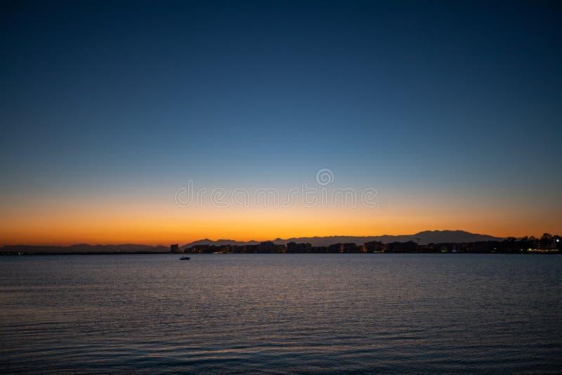 Sen solnedgånghimmelsikt över ett lugna hav arkivbild