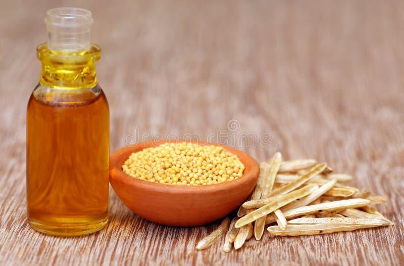 Senape dorata con i baccelli e l'olio vuoti in una bottiglia fotografia stock libera da diritti