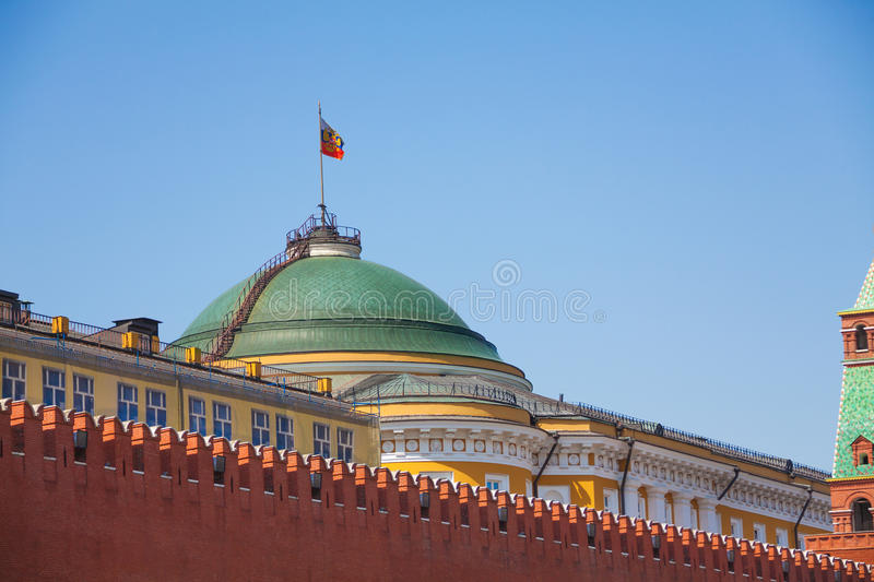 Senate palace with Russian flag in Moscow Kremlin. Senate Palace with Russian flag and red brick Kremlin wall behind it in Moscow, Russia royalty free stock images