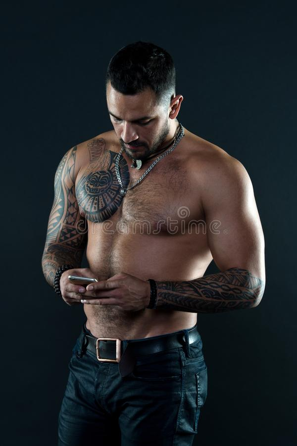 Send message. Handsome fit man send message smartphone. Muscular tattooed athlete look attractive. Messaging stock photo