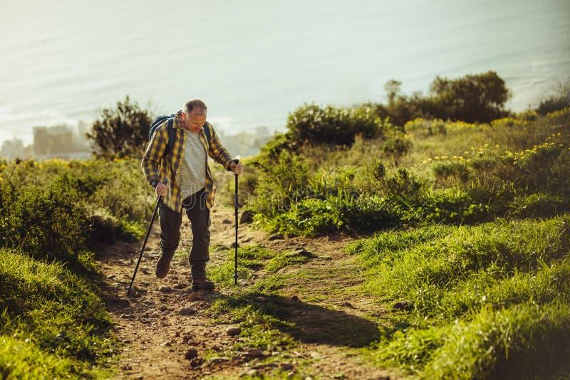 Senderismo del hombre encima de una colina usando caminar polos imagenes de archivo
