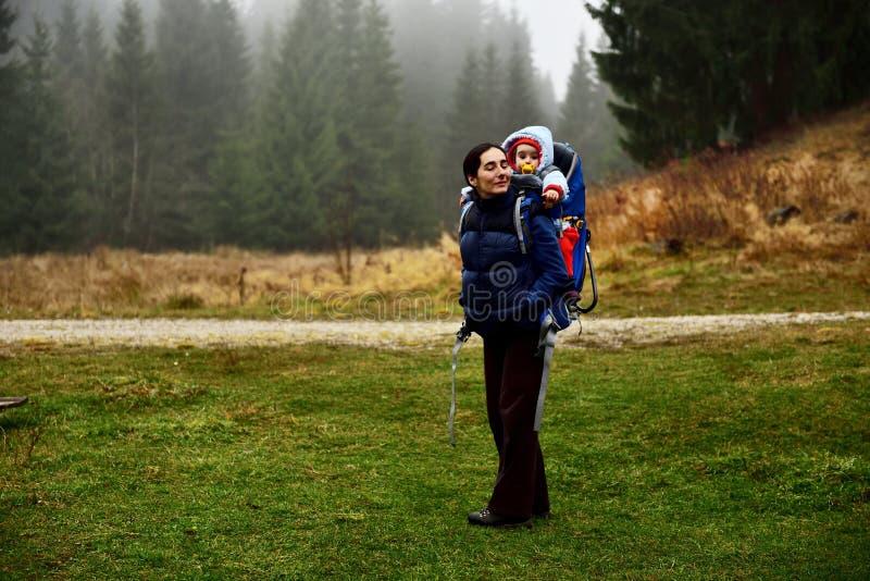 Senderismo joven de la madre, llevando a su bebé en una mochila del bebé foto de archivo libre de regalías