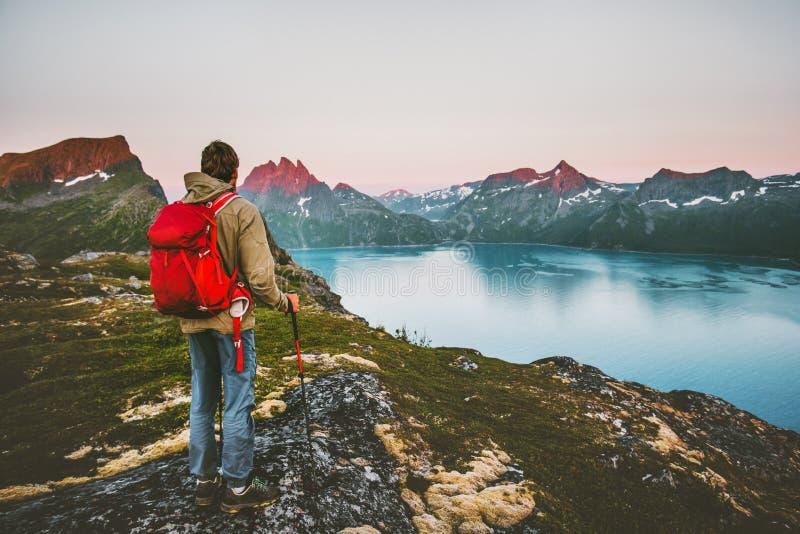 Senderismo turístico del hombre del descubridor en montañas de la puesta del sol foto de archivo libre de regalías