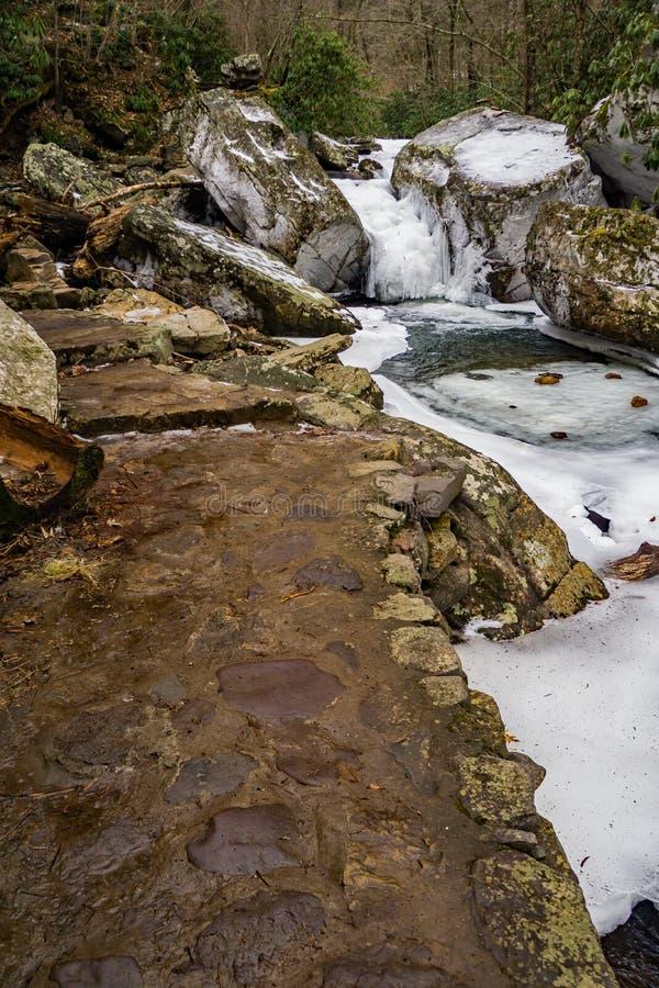 Sendero de piedra por una cala congelada imagenes de archivo