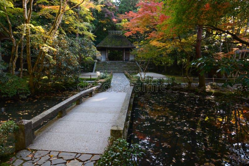 Sendero y puente de piedra sobre una pequeña charca japonesa durante otoño en Kyoto fotos de archivo