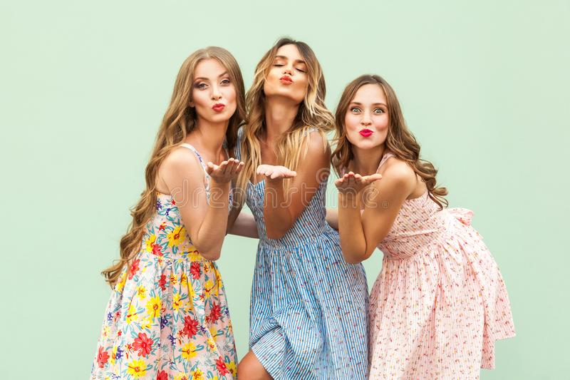 Sending air kiss. Three best friends posing in studio, wearing summer style dress against green background. stock images