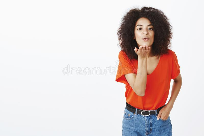 Sending best wishes to all fans. Portrait of outgoing good-looking african-american female model with afro hairstyle. Bending towards camera, holding hand in stock photography